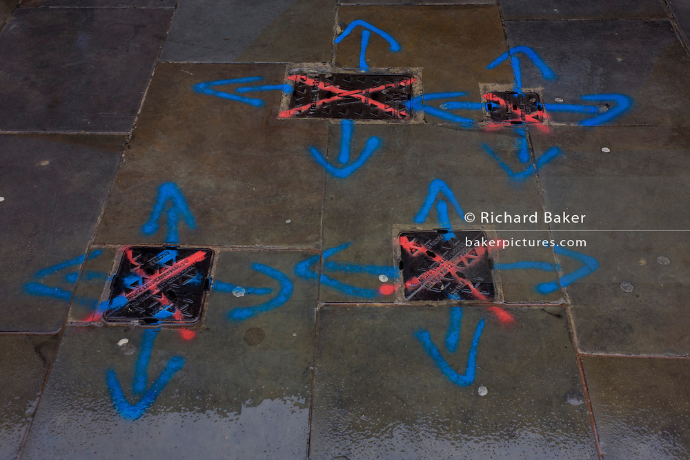 Sprayed markings showing water covers on a City of London pavement where workem will soon be digging.
