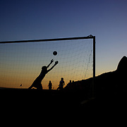 Locals play football during the late afternoon sunset on Ipanema beach, Rio de Janeiro,  Brazil. 7th July 2010. Photo Tim Clayton..The beaches of Rio de Janeiro, provide the ultimate playground for locals and tourists alike. Beach activity is in abundance as beach volley ball, football and a hybrid of the two, foot volley, are played day and night along the length and breadth of Rio's beaches. .Volleyball nets and football posts stretch along the cities coastline and are a hive of activity particularly at it's most famous beaches Copacabana and Ipanema. .The warm waters of the Atlantic Ocean provide the ideal conditions for a variety of water sports. Walkways along the edge of the beaches along with exercise stations and cycleways encourage sporting activity, even an outdoor gym is available at the Parque Do Arpoador overlooking the ocean. .On Sunday's the main roads along the beaches of Copacabana, Leblon and Ipanema are closed to traffic bringing out thousands of people of all ages to walk, run, jog, ride, skateboard and cycle more than 10 km of beachside roadway. .This sports mad city is about to become a worldwide sporting focus as they play host to the world's biggest sporting events with Brazil hosting the next Fifa World Cup in 2014 and Rio de Janeiro hosting the Olympic Games in 2016...