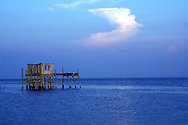 The sun sets on a stilt house in the Gulf of Mexico near Cedar Key, Florida.  The cloud above appears to be an angel.