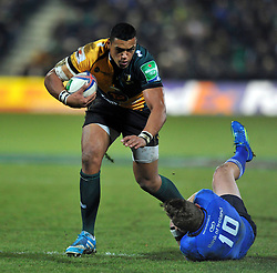 Luther Burrell (Northampton) is tackled around the leg by Ian Madigan (Leinster) - Photo mandatory by-line: Patrick Khachfe/JMP - Tel: Mobile: 07966 386802 07/12/2013 - SPORT - RUGBY UNION -  Franklin's Gardens, Northampton - Northampton Saints v Leinster - Heineken Cup.