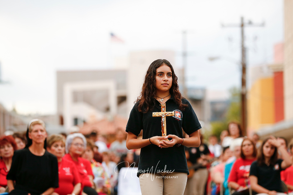 A young woman carries a crucifix in the offertory during Mass at the international border in Nogales, Arizona, Oct. 23. The cross was presented to recall migrants who have died in the deserts of Arizona. (CNS photo/Nancy Wiechec)