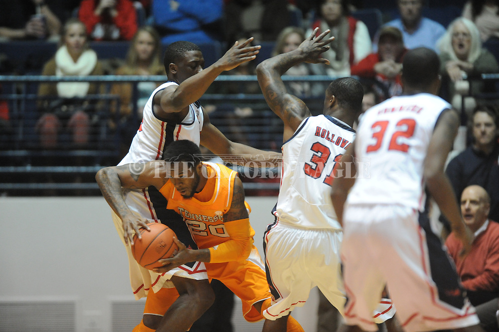 """Tennessee's Kenny Hill (20)  is fouled by Mississippi's Murphy Holloway (31) as Mississippi's Reginald Buckner (23) also defends at the C.M. """"Tad"""" Smith Coliseum on Thursday, January 24, 2013. (AP Photo/Oxford Eagle, Bruce Newman)"""