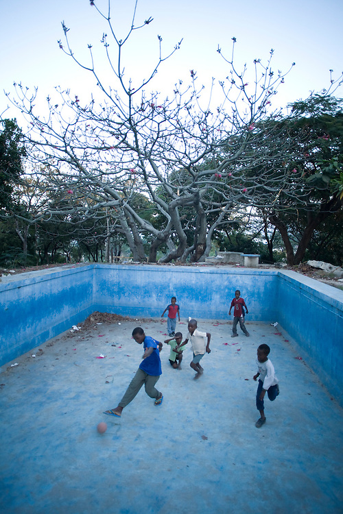Children play soccer in the empty pool of the old Italian Embassy which collapsed during the earthquake in Nerettes, Haiti. Photo by Ben Depp 2/6/2010