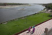 Three women are walking inside the Taj Mahal complex where, in the original design, there was supposed to be water to keep the Taj from falling towards the heavily polluted Yamuna River, in Agra.