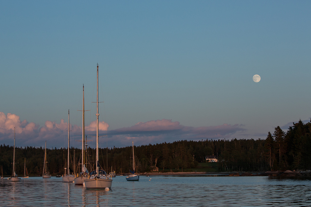 Center Harbor, Maine - 9 August 2014. The moon rising at sunset.