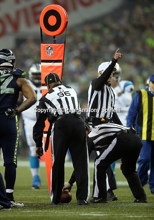 Referee Terry McAulay (77) signals first down as umpire Undrey Wash (96) and another official measure for a Carolina Panthers first down on a fourth down play in the second quarter during the NFL week 19 NFC Divisional Playoff football game against the Seattle Seahawks on Saturday, Jan. 10, 2015 in Seattle. The Seahawks won the game 31-17. ©Paul Anthony Spinelli