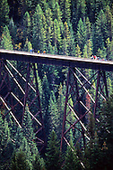 Bicyclists on train trestle along Route of the Hiawatha Rails to Trails route. Shoshone County, north Idaho.