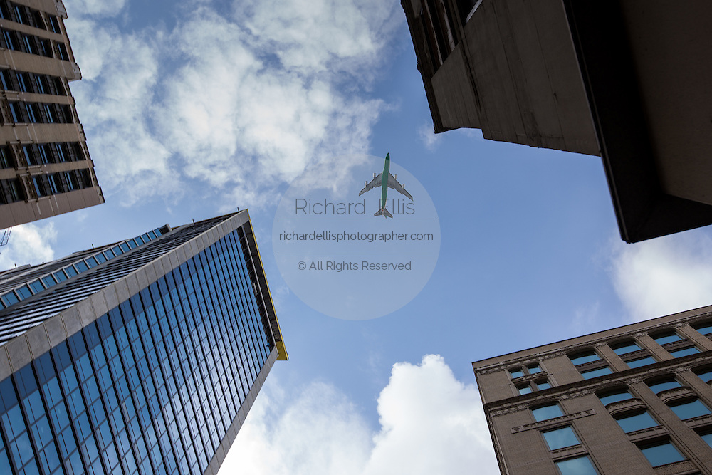 A commercial passenger jet passes overhead skyscrapers in the Loop District downtown Chicago, IL.
