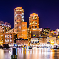 Boston skyline at night panoramam picture with the Boston Harborwalk waterfront, downtown Boston skyscrapers and Nothern Avenue Bridge. Panoramic photo ratio is 1:3.