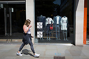 As the UK's Coronavirus death toll during the government's social distancing lockdown, rose by 384 to 33,998, and the R rate of infection is reported to be between 0.7 and 1.0, a woman walks past clothing mannequins in the window of a closed branch of Ted Baker, are covered in polythene plastic, in the City of London, the capital's now empty financial district, on 15th May 2020, in London, England.