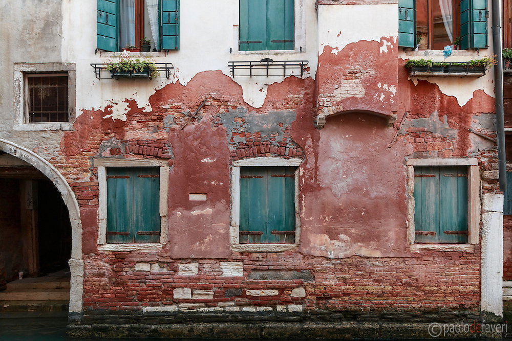 The facade of an old building facing a canal in the sestiere (district) of Cannaregio in Venice, Italy