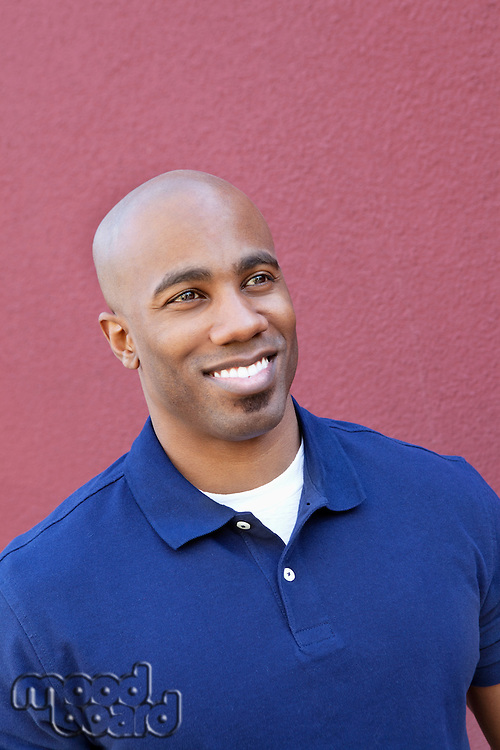 Happy bald African American man looking away over colored background