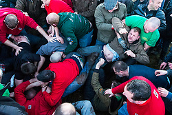 © Licensed to London News Pictures. 06/01/2018. Haxey UK. A man winces in pain as he is kicked in the groin at the start of the start of The Haxey Hood game that is taking place today in the village of Haxey in Lincolnshire. The Haxey Hood is a traditional event that takes place every January & is played by teams from four pubs, the Carpenters Arms, the Duke William Hotel, The Loco & The kings Arms. The game is like a large rugby scrum called the 'sway' which pushes a leather tube called the 'hood' to one of the four pubs, the game is won when a team gets the hood to the front step of the pub & it is touched by the landlord.  Photo credit: Andrew McCaren/LNP