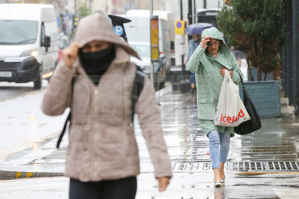 © Licensed to London News Pictures. 27/06/2020. London, UK. Women shelter from rain underneath jacket hoods in north London following a very hot week which saw highest temperature of the year so far. Photo credit: Dinendra Haria/LNP