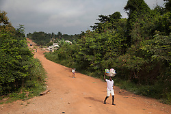 People walk on a road just near the town of Bosomkyekye. CARE has several programs in this area, including the REGAL program for students and a training program for teachers. In addition, a school in Bosomkyekye was the site of the art project done in conjunction with the celebration for CARE's 20th anniversary in Atlanta.