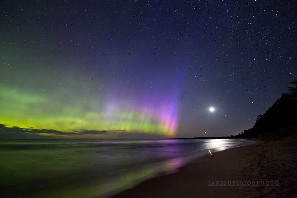 The aurora borealis northern lights puts on a beautiful display of vivid color as the moon and Venus rises over Lake Superior in Marquette, Michigan in the Upper Peninsula