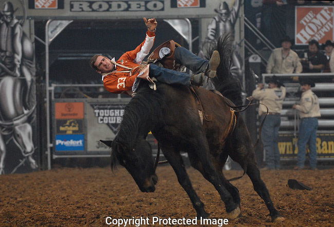 Tough cowboy Dusty Elkinton shows extreme calm as he balances sideways on a horse during the bareback bronc riding event.
