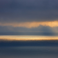 Mystical and misty Sunset over Atlantic with golden sunbeams shining on the peacefull water surface / wt029