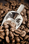 A small measuring or sampling shovel, metallic spatula placed into the heap of coffee beans.
