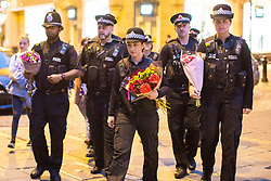 © Licensed to London News Pictures . 29/05/2017 . Manchester , UK . Police arrive with flowers to pay their respects ahead of a vigil at 10:31pm in St Ann's Square in Manchester City Centre , exactly a week after Salman Abedi murdered 22 and injured another 64 at an Ariana Grande concert at Manchester Arena . Photo credit: Joel Goodman/LNP