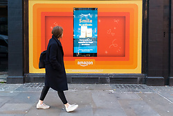 © Licensed to London News Pictures. 23/11/2018. London, UK.  A woman walks past the Amazon.com Black Friday pop-up shop on Shoreditch High Street in London this morning.  Photo credit: Vickie Flores/LNP