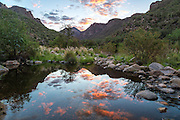 Sunlit clouds reflect in the still water of Bear Creek along the trail to Seven Falls in the Santa Catalina mountains