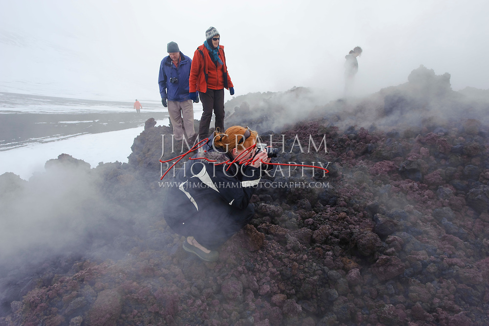 Tourists inspect a lava field at the volcano near the Eyjafjallajoekull glacier on Monday 12 April 2010.  The Volcano had been erupting for the past 3 weeks and is now qiet, although earthquakes continue to rumble throughout the region. Photo by Jim Graham.