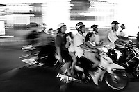 Family of four riding a motorbike in the blur of Saigon traffic at night.