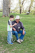 Richard Real Bird, teaching grandson Hudson to yoyo, alongside Little Bighorn River, at Medicine Tail Coulee site of Battle of the Little Bighorn, Crow Indian Reservation, Montana