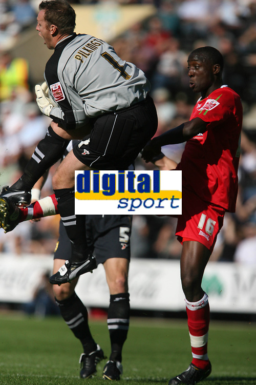 Photo: Pete Lorence.<br />Notts County v Swindon Town. Coca Cola League 2. 23/09/2006.<br />Kevin Pilkington leaps over the Swindon attack, led by Fola Onibuje.