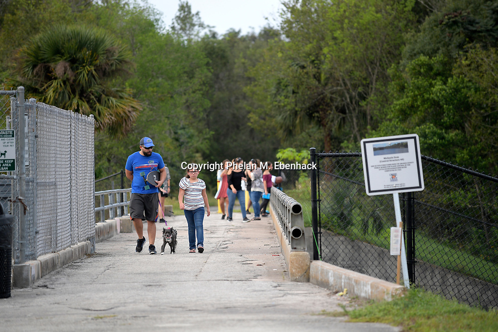 Pedestrians walk along a bridge over the Little Econlockhatchee River in Jay Blanchard Park Saturday, Oct. 21, 2017, in Orlando, Fla. (Photo by Phelan M. Ebenhack)