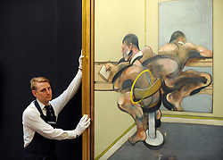 © Licensed to London News Pictures. 12/04/2012. London, UK . A Sotheby's employee holds Francis Bacon's 'Figure Writing Reflected in Mirror'  which is expected to fetch 30 - 40 million US dollars. Photocall for Sotheby's Impressionist and Modern Art Evening Sale 12 April 2012. Photo credit : Stephen Simpson/LNP