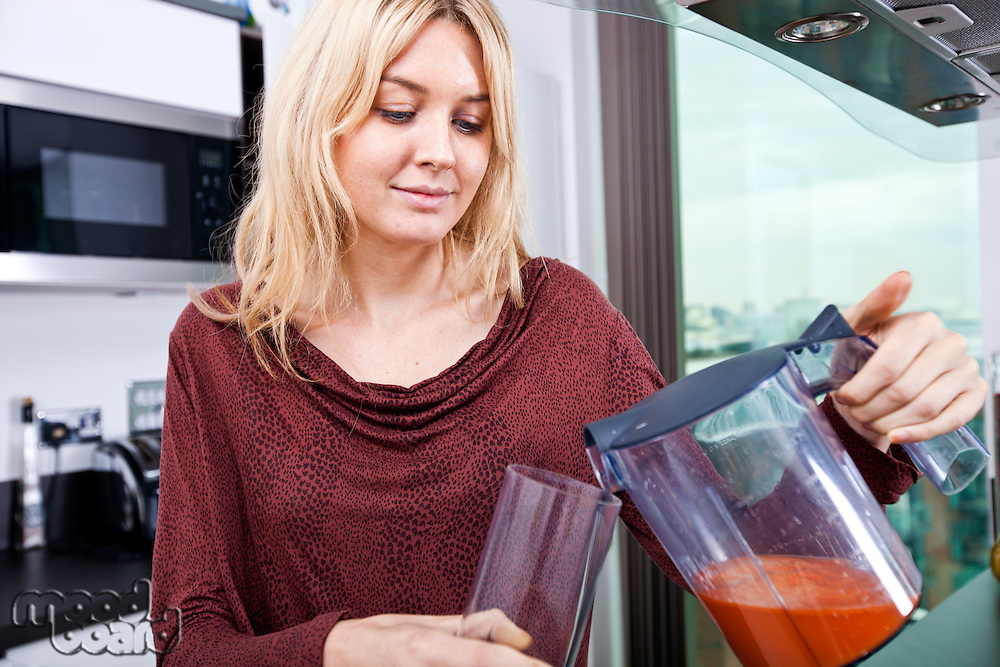 Young woman pouring carrot juice in glass at kitchen