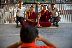 Indians take photos with monks at the Namgyal Monastery, opposite the Dalai Lama's residence in McLeod Ganj, Dharamsala, India, where the Dalai Lama settled after fleeing Tibet in 1959 after a failed uprising against Chinese rule, June 3, 2009.