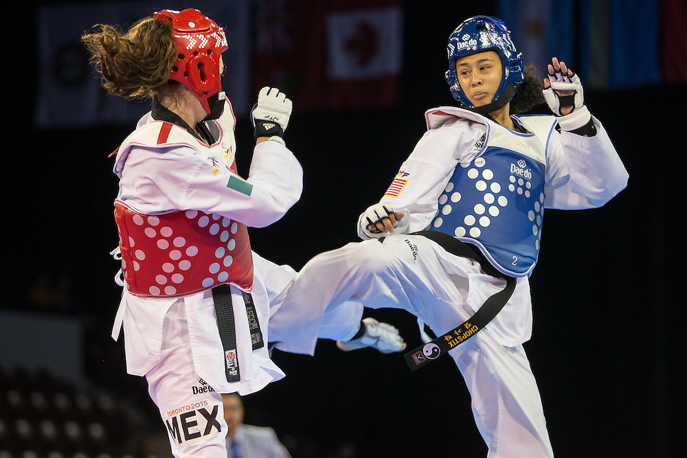 Cheyenne Lewis (R) of the United States kicks  Paulina Armeria of Mexico during their gold medal contest in the women's -57kg weight division of Taekwondo at the 2015 Pan American Games in Toronto, Canada, July 20,  2015.  AFP PHOTO/GEOFF ROBINS