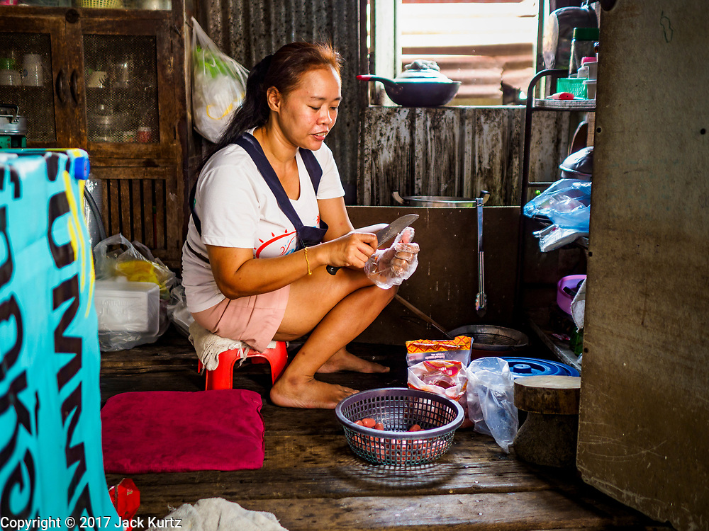 """21 JUNE 2017 - BANGKOK, THAILAND: A woman slices sausages in her home in a community along the Chao Phraya River south of Krung Thon Bridge. This is one of the first parts of the riverbank that is scheduled to be redeveloped. The communities along the river don't know what's going to happen when the redevelopment starts. The Chao Phraya promenade is development project of parks, walkways and recreational areas on the Chao Phraya River between Pin Klao and Phra Nang Klao Bridges. The 14 kilometer long promenade will cost approximately 14 billion Baht (407 million US Dollars). The project involves the forced eviction of more than 200 communities of people who live along the river, a dozen riverfront  temples, several schools, and privately-owned piers on both sides of the Chao Phraya River. Construction is scheduled on the project is scheduled to start in early 2016. There has been very little public input on the planned redevelopment. The Thai government is also cracking down on homes built over the river, such homes are said to be in violation of the """"Navigation in Thai Waters Act."""" Owners face fines and the possibility that their homes will be torn down.          PHOTO BY JACK KURTZ"""