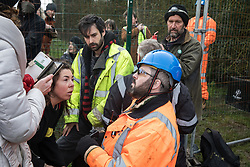 Harefield, UK. 8 February, 2020. Environmental activists seek to calm a HS2 engineer who reacted adversely to some of them crawling through a ditch under a road closure implemented on Harvil Road in the Colne Valley to facilitate tree felling works for the high-speed rail project. Environmental activists based at a series of wildlife protection camps in the area prevented the tree felling works for the duration of the weekend for which they were scheduled.