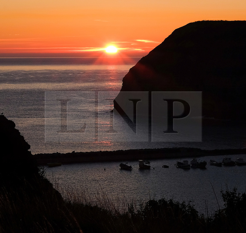© Licensed to London News Pictures.02/10/15<br /> Staithes, UK. <br /> <br /> Fishing boats are moored in the harbour as the sun rises over the North Yorkshire village of Staithes on the east coast as the warm autumn weather continues.<br /> <br /> Photo credit : Ian Forsyth/LNP