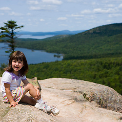 A young girl (age 5) on the South Bubble in Maine's Acadia National Park.  Eagle Lake is in the distance.
