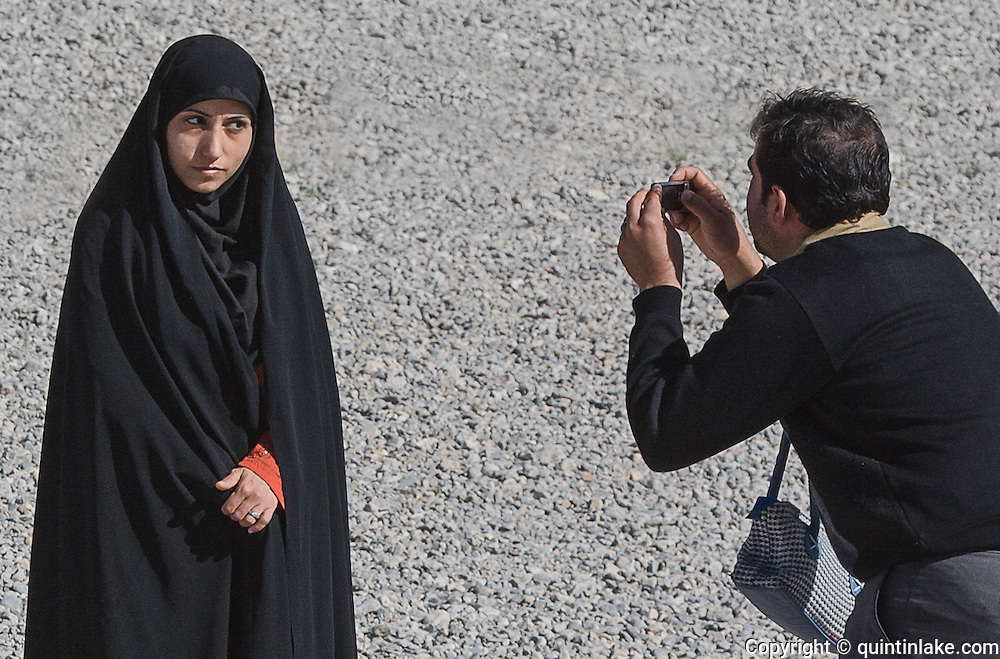 A lady wearing a chador posing for a photo at Persepolis (detail). Persepolis was the ceremonial capital of the Persian Empire (550-330 BC) during the Achaemenid dynasty. Persepolis, Iran, 2008
