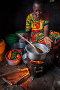 At her home near Arusha, Tanzania Solar Sister entrepreneur Julieth Mollel  prepares a dinner of ugali, vegetables and beans cooking on her clean cookstove. Ugali is a staple eaten in many countries in Africa and is cornmeal porridge. Working in her compact outdoor kitchen at night is easier now with the clean cookstove that puts out very little smoke and uses only a fraction of the firewood of a traditional three-stone cookstove.                                                 Julieth Mollel stands tall when she says she is a Solar Sister Entrepreneur and her success in selling the lanterns and cookstoves has given her hope for her future and the future of her grandchildren.<br /> <br /> Julieth Mollel has not had an easy life. Julieth and her husband are from the Masai tribe and live in northern Tanzania about an hour outside of Arusha near the southern slopes of Mount Meru. Julieth has toiled all of her life farming, selling crops and keeping the house for her husband and children. Now at sixty-one (61) she works hard to keep the family going and to pay the fees to send her grandchildren to school.<br />  <br /> Until she started working for Solar Sister in Tanzania life was becoming almost unbearable for Julieth. Cooking over her traditional cook stove made of three stones and an open fire pit put out a lot of smoke that she breathed in when she cooked breakfast, lunch and dinner for her family. <br /> <br /> The stove required a lot of firewood so daily she had to go out and bring home a huge bundle of wood. Over time she began to have severe pains in her chest and had difficulty picking up and carrying the firewood back home. Juileth has had to walk farther and farther to get firewood as the years have passed due to the cutting down of trees in the area to expand farms and build settlements as well as the collection of firewood for cooking and making charcoal.<br /> <br />  During this time Julieth was struggling to still pay the fees for her grandchildren to 