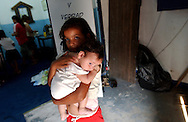 A Paraguayan girl holds a baby in the Asociacion Cultural Justicia y Verdad (Association of Cultural Justice and Truth) in Asuncion, Paraguay on Friday evening, March 17, 2006. The shelter founded by Dr. Chantal Hulin, is run out of a renovated auto garage, where volunteers provide showers, administer health care, simple meals, and classroom activities to some of the hundreds of homeless street children that panhandle and clean windshields for money on the neighborhood streets.