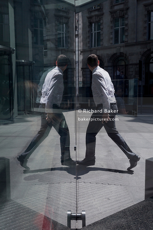 A financial industry businessman walks past the sculpture entitled City Wing on Threadneedle Street in the City of London, the capital's financial district (aka the Square Mile), on 11th July 2019, in London, England. City Wing is by the artist Christopher Le Brun. The ten-metre-tall bronze sculpture is by President of the Royal Academy of Arts, Christopher Le Brun, commissioned by Hammerson in 2009. It is called 'The City Wing' and has been cast by Morris Singer Art Founders, reputedly the oldest fine art foundry in the world.