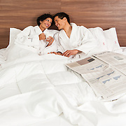 Advertising photography for Hotel Elan. Photo of couple laying in bed with breakfast and newspapers at Hotel Elan.<br />