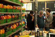 Three men ponder samples at Toronto's St. Lawrence farmers' market, framed by baskets of red, green and yellow bell peppers.