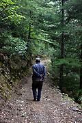 Farmer walking in the woods near Xidang Spring, Yunnan, China; September, 2013.