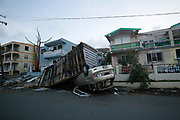 An upturned car lies crushed underneath a shipping container outside a house, on the British Virgin Island of Tortola, 11 September 2017. The island was badly damaged by Hurricane Irma on 6 September.