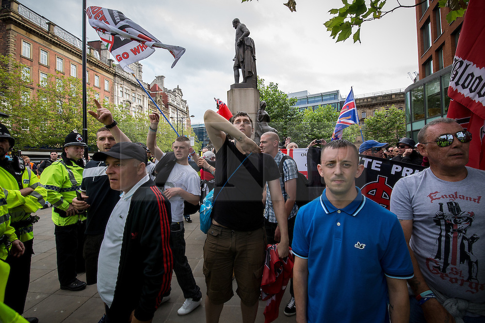 "© Licensed to London News Pictures . 22/08/2015 . Manchester , UK . A far-right supporter (c) gives a Nazi salute . Far-right nationalist group , "" North West Infidels "" and Islamophobic , anti-Semitic and white supremacist supporters , hold a rally in Manchester City Centre . Photo credit : Joel Goodman/LNP"