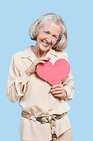Portrait of senior woman holding red paper heart against blue background