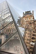 An unusual view through a wall of the glass pyramid into the subterranean entrance of the Louvre museum, while another wall of the pyramid reflects the old palace walls.